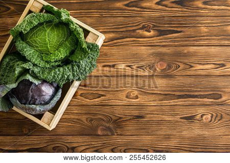 Two Fresh Heads Of Savoy And Red Cabbage Side By Side In A Wooden Box On A Table At Wooden Table At