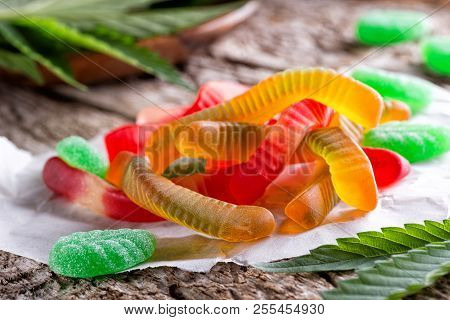 Cannabis Infused Gummy Candy On A Rustic Table Top With Marijuana Leaves.
