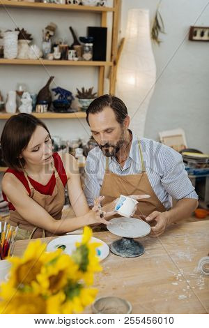 Female And Male Ceramists Finishing Their Work With Decorations