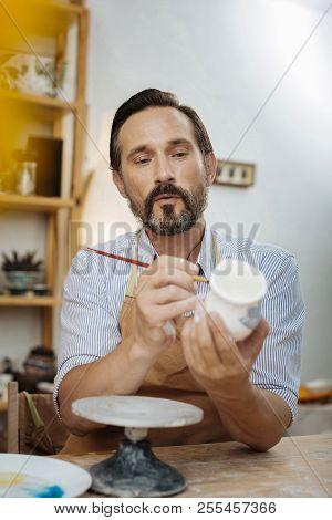 Dark-eyed Bearded Ceramist Wearing Apron And Working