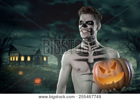 Sport And Health Food, Halloween Gourd. Young Man With Muscular Body And Pumpkin. Strong Man Body. N