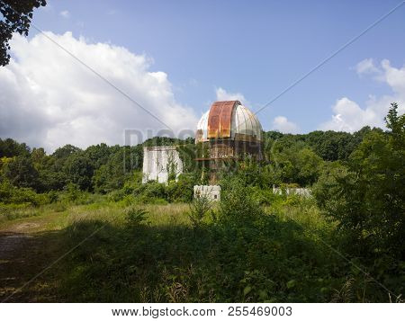 Trees And Vegetation Overrunning A Rusting, Abandoned Observatory Under The Clouds And Blue Sky