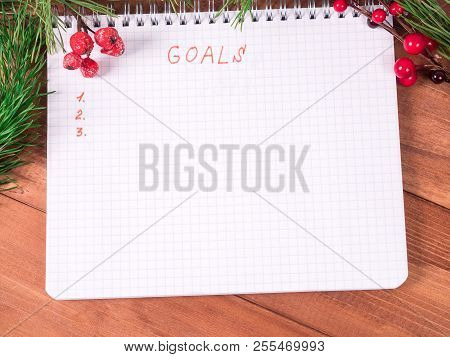 Notepad For Writing Resolution And Goals For The New Year, Spruce Branches On A Wooden Background Wi
