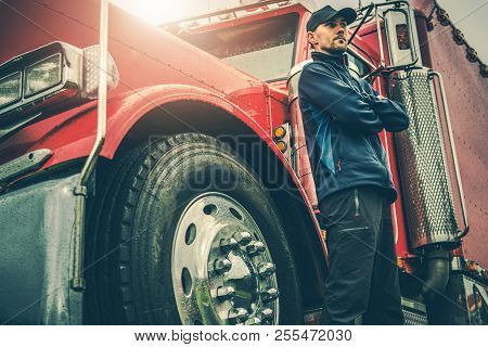 American Trucker Proud. Semi Truck Driver In Front Of His Awesome Machine. Transportation Industry T