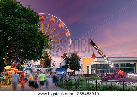 Attraction Ferris Wheel On Summer Evening In City Amusement Park.