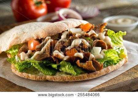A Delicious Doner Meat Sandwich On Pita Bread With Lettuce, Tomato, Onion And Sauce.