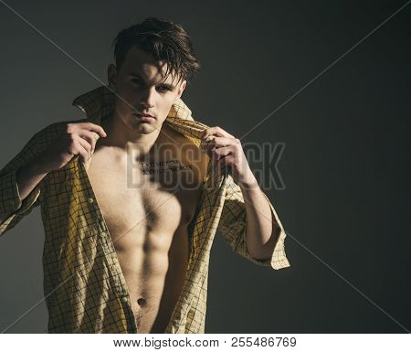 Masculine concept. Guy looks confident and attractive. Man with torso, muscular macho with six packs, dressing shirt, dark background. Macho on pensive face, muscular figure, sportsman, bodybuilder. poster