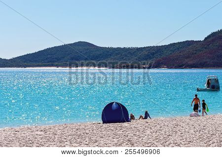 Tourists Relaxing In Front Of A Small Blue Shade Tent On The White Silica Sand Beach In Whitsunday I