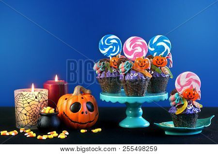 Halloween Candyland Drip Cake Style Cupcakes With Candy On Blue Background.