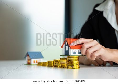 Concept For Property Ladder, Mortgage And Real Estate Investment. Woman's Hand Putting House Model O