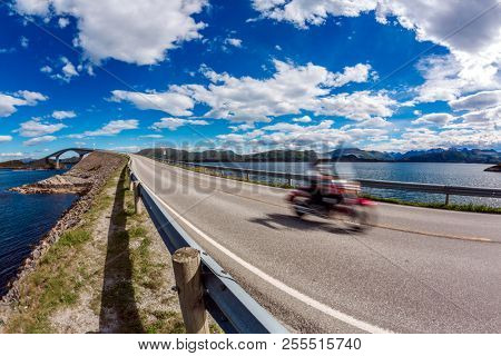 Biker rides a road with Atlantic Road in Norway. Atlantic Ocean Road or the Atlantic Road (Atlanterhavsveien) been awarded the title as Norwegian Construction of the Century. Biker in motion blur.