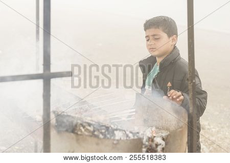 Gilan Province- Iran-july 23, 2018 Portrait Of A Teenage Boy Making Kebab In Fogy Day Beside Travel