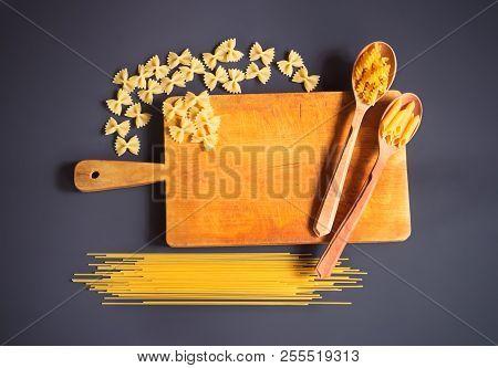 Cutting Board And Raw Pasta On Dark Background.
