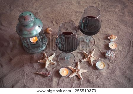 Romantic Beach Evening: Two Glasses Of Wine, Candles, Lantern, Shells, Starfishes. Valentines Day.