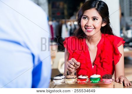 Portrait of a cheerful Asian woman ordering cupcakes behind the counter in a cool coffee shop with various delicious confections   poster