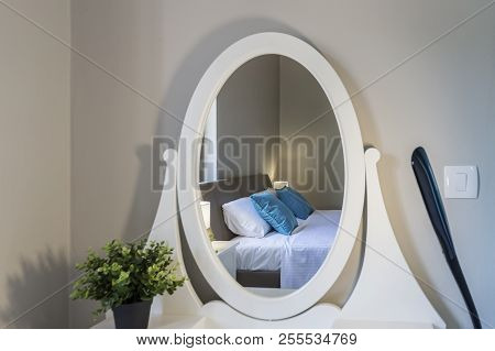Room With Comfortable Bed Reflected In The Mirror