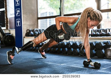 Portrait of fitness handicapped sportsgirl with prosthesis in tracksuit doing push ups with dumbbells in gym