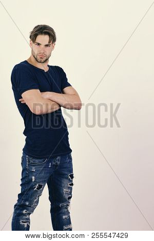 Man with fair hair on white background. Masculinity and confidence concept. Guy in dark blue tshirt and jeans. Macho with confident face and crossed arms, copy space poster