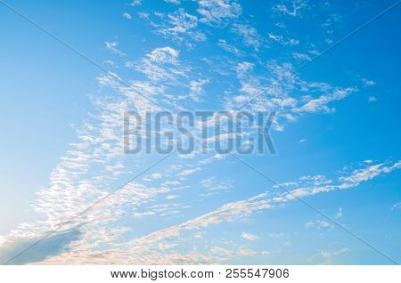 Blue sky sunset landscape with dramatic clouds lit by evening sunset light - colorful evening sky view. Sky landscape scene, blue sky background with white clouds in the sky lit by sunlight. Natural sky background, sky sunny landscape.Sunny sky background
