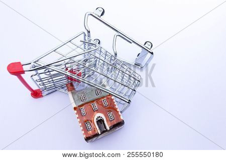 Miniature Shopping Trolley On Its Side With A Miniature House Falling Out.