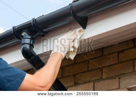 Property Maintenance - Close Up Of A Man Cleaning A Gutter On A House.
