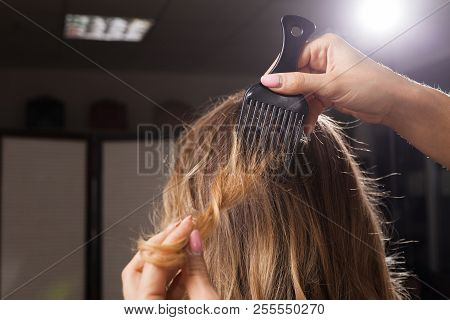 close up photo of professional hairdresser brushing hair of a model with waving coiffure in a beauty salon at a master class. concept of stylist training poster