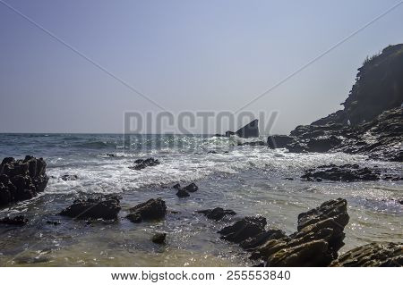 Sea Beach On Bay Of Indian Ocean, Goa, India. Emerald Waves Of Ocean Under Blue Sky. Rocky Coastline