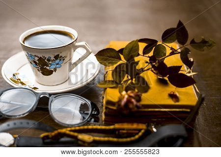 Close Up Of Book With Reading Glasses And Cup Of Coffee With A Rose Flower On Wooden Surface.concept