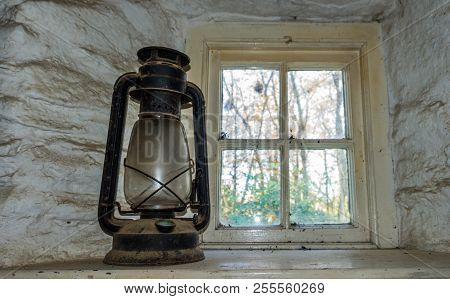 A Vintage Oil Lantern On A Shelf Near A Small Square Window