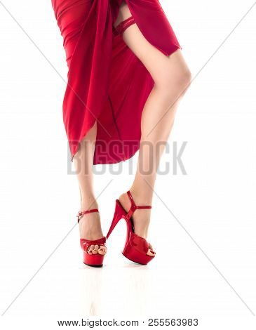Woman In Red Dress With Sexy Legs Isolated On White Background. On Her Leg Red Garter. Garter On Her