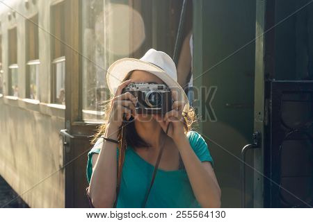 Girl in vacation. Traveler girl in vacation taking photo in train station. Young woman in vacation. Lifestyle concept. Vacation concept. Lifestyles. Vacations. Holiday. Girl traveling alone in train station taking photo.