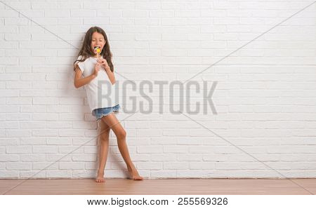 Young hispanic kid over white brick wall eating lollipop candy at home with a confident expression on smart face thinking serious
