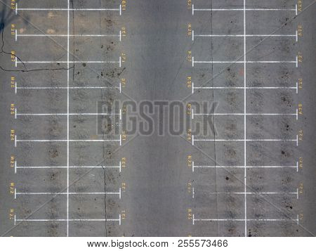 Panoramic view from drone above empty parking with white marking lines on asphalt with numbered places. Parking cars background.