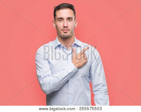 Handsome young businessman cheerful with a smile of face pointing with hand and finger up to the side with happy and natural expression on face looking at the camera.