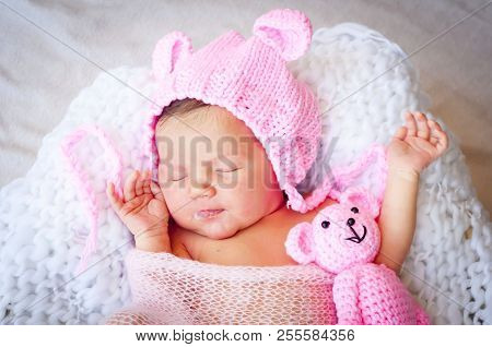 Cute Sleeping Newborn Caucasian Baby Girl In A Pink Hat With Ears Holding A Teddy Bear. Sweet Infant