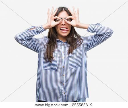 Young beautiful hispanic business woman doing ok gesture like binoculars sticking tongue out, eyes looking through fingers. Crazy expression.