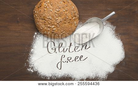 Loaf Of Healthy Bread And Gluten Free Flour Scattering From Scoop, Top View