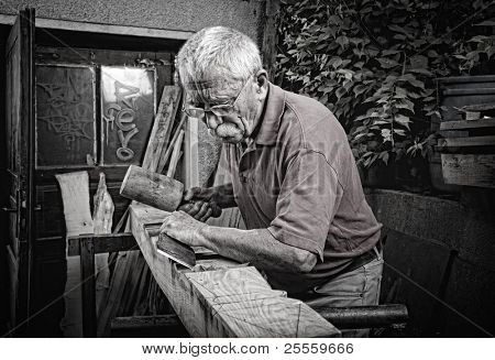 Old woodcarver working with mallet and chiesel, vintage style