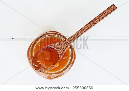Overhead Shot Of A Wooden Spoon Full Of Homemade Cantaloupe Jam Resting In An Open Jar Filled With J