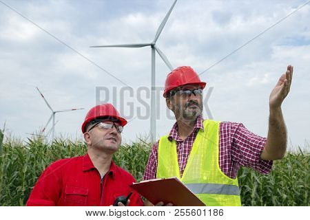 Engineer Holding Clipboard Standing With Coworker At Wind Farm. Engineer In Safety Hard Hat Pointing
