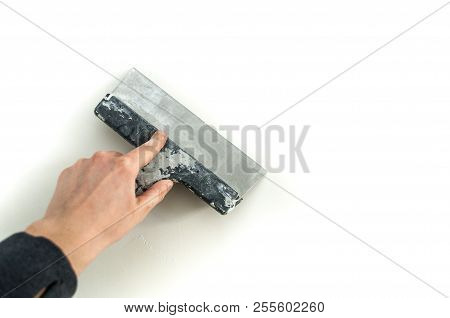 Man Plastering The Walls With Finishing Putty In The Room With Putty Knife Or Spatula. Repair Work,