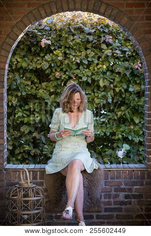 Beautiful Woman Sitting In A Arch Of A Frontporch Reading A Book