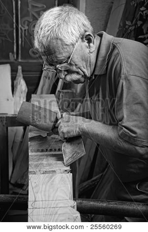 Stock Photo: Old woodcarver working with mallet and chisel