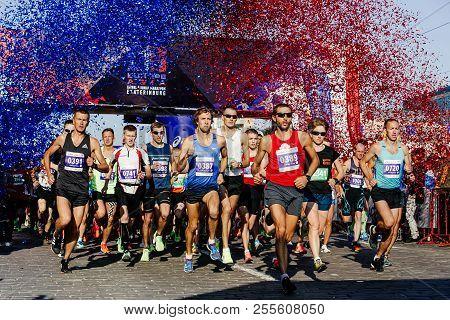 Ekaterinburg, Russia - August 5, 2018: Start Of Marathon Group Runners Under Fireworks Of Confetti I