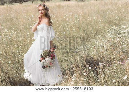 Beautiful Pensive Young Bride In Wedding Dress And Floral Wreath Holding Bouquet Of Flowers While St