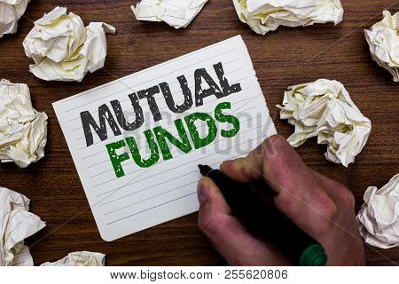 Conceptual hand writing showing Mutual Funds. Business photo showcasing An investment program funded by shareholders Individual Stocks Man holding marker notebook page crumpled papers mistakes. poster