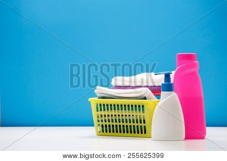 Photo of pink and white bottle for cleaning products and yellow basket with towels on empty blue background