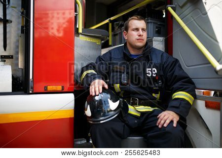 Photo of young firefighter looking to side with helmet in overalls sits in fire truck