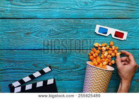 People eating popcorn. Human hands. Top view