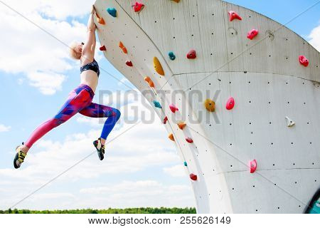 Photo of sporty blonde in leggings hanging on wall for rock climbing against blue sky